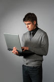 Work. Young businessman with laptop; isolated on gray Stock Photo