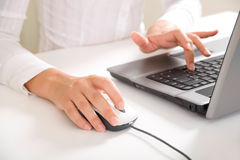 Work. Close-up of feminine hands typing on laptop keyboard and touching mouse Royalty Free Stock Photo
