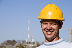At work. Smiling young man in a helmet. People at work Stock Image