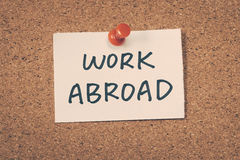 Work Abroad. Note pin on the bulletin board stock photo