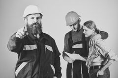 Work abroad. Recruitment concept. Brigade of workers, builders in helmets, repairers and lady discussing contract, grey. Background. Brigadier hiring workers Royalty Free Stock Photo