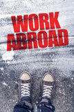 Work abroad title on the pavement. Above which is young male student standing and making decision to travel to foreign country and find a job stock photos