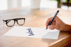 Work  against side view of hand writing on white page on working desk Royalty Free Stock Image