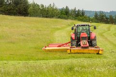 Work on an agricultural farm. A red tractor cuts a meadow. stock photo