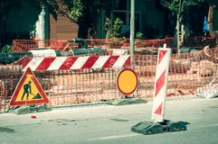 Work ahead street reconstruction site with sign and fence as road barricade. Work ahead street construction and reconstruction site with warning sign dead end royalty free stock images