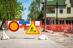 Work ahead street district heating pipeline reconstruction site with sign and fence as road barricade.  stock photography