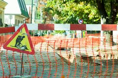 Work ahead street reconstruction site with sign and fence as road barricade. Royalty Free Stock Image