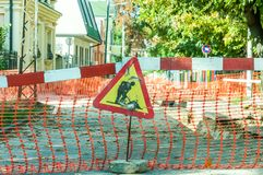 Work ahead street reconstruction site with sign and fence barricade. Stock Photos