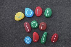 Work for all ! Social slogan with multicolored stones over black volcanic sand. Work for all, usual politics promise and international slogan for present and Stock Image