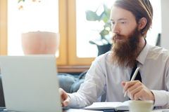 Work of analyst. Businessman analyzing online data and making notes stock photography
