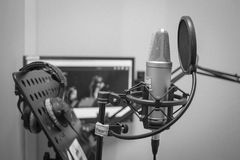 The work of the announcer and actor of voice acting and dubbing in front of the microphone. Professional microphone close-up. The actor`s act of dubbing and royalty free stock photography
