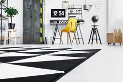 Work area with metal wardrobe. Low angle of black and white carpet in open work area with yellow chair at desk and metal wardrobe royalty free stock photo