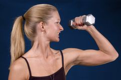Work that arm!. Woman with weights staying in shape Royalty Free Stock Image