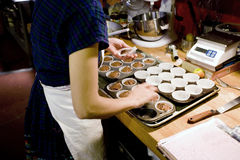 At Work in the Bakery. Photo of a baker making muffins in the bakery Stock Photography
