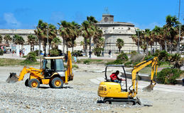 Work on the beach. Scrapes in action for cleaning a beach stock photos