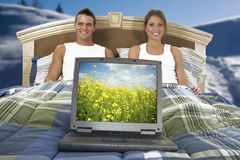 Work in bed. Young couple in bed with laptop in front pan, scenery background royalty free stock photos
