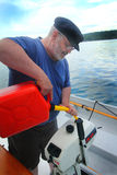 Work on the Boat. A closeup of an older scruffy man wearing a wool captain's bill cap and glasses on the water pouring gas in a small outboard motor.  Shallow Royalty Free Stock Photography