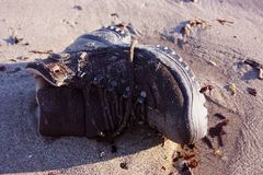 Work boot. object of clothing abandoned among the dirt on a sandy beach stock photo