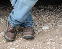Work boots. Man in dirty work boots and jeans standing on a dirt road Royalty Free Stock Photo