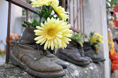 Work boots. With yellow flower on the wall blacks used worn old antique finished Royalty Free Stock Photos