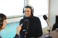 Work broadcaster and chat with interesting guests for recording. Cute female radio host and funny guy with headphones and talking are direct inclusion of radio Royalty Free Stock Photo