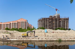 Panorama of a building site and the construction crane in a clear sunny day Royalty Free Stock Photos