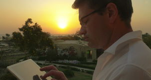 Work on business with pad outdoor at sunset. Young man putting on glasses to start his work with digital tablet on resort at sunset. Business matters on vacation stock footage