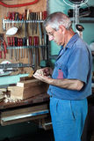 Work cabinetmaker looking handcrafted wooden pieces finished in Stock Images