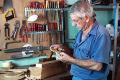Work cabinetmaker looking handcrafted wooden pieces in garage at Royalty Free Stock Photos