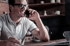 Adult businessman talking with client on phone. Work is calling. Positive minded millennial guy smiling while taking some notes and having a pleasant Stock Images