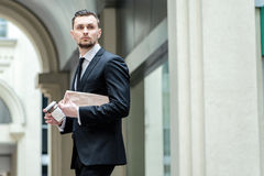 Work can not wait. Confident businessman holding a newspaper and Royalty Free Stock Photos