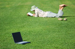 Work can wait!. Laptop on the Green Grass and a Woman Lays in the Grass Reading stock images