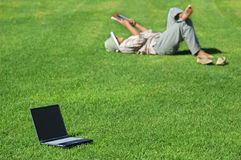 Work can wait!. Laptop on the Green Grass and a Woman Lays in the Grass Reading royalty free stock images