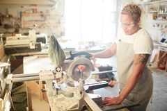 Work of carpenter. Young carpenter using electric circle saw while working with wooden plank royalty free stock image