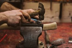 Work in carpentry shop. Man working in carpentry workshop. He attaches leather winding on wooden handle of an ax. Men at work. Hand work Royalty Free Stock Photo