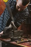 Work in carpentry shop. Man working in carpentry workshop. He expands slit for the wedge in wooden handle of ax. Men at work. Hand work Royalty Free Stock Photography