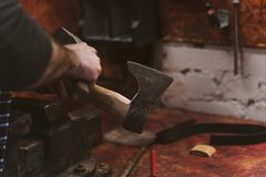 Work in carpentry shop. Man works in carpentry workshop. He straightens ax blade on wooden handle with hammer. Men at work. Hand work Royalty Free Stock Photography