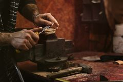 Work in carpentry shop. Man works in carpentry workshop. He cuts off excess wood with knife with an ax Royalty Free Stock Images