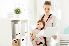 Work and childcare. Funny baby girl in carrier spending day with her business mother in office royalty free stock photography