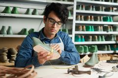 Work of cobbler. Young cobbler measuring shoe by workplace in his own studio stock images