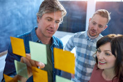 Work colleagues brainstorming with sticky notes in a modern office. Three casually dressed work colleagues brainstorming together on a glass wall with sticky royalty free stock photo