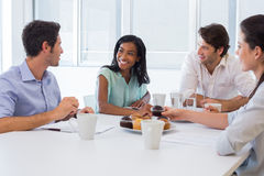 Work colleagues chatting in board room while enjoying coffee and muffins Royalty Free Stock Photos