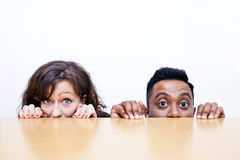 Work colleagues peeking over edge of table Stock Image
