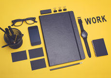 Work concept. Office items design mockup. Black office items arranged on a yellow background stock photo