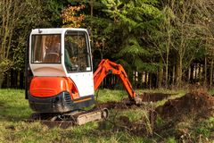 Work on the construction site of an ecological house. The excavator adjusts the terrain. A small digger in the garden. Work on the construction site of an royalty free stock photo