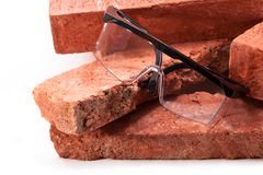 Work on the construction site. Red clay bricks dismantled from old buildings and goggles Royalty Free Stock Image