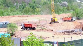 Work on the construction site. Trucks are actively moving around the construction site. Work on the construction site. Trucks are actively moving around the stock video