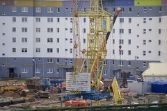 Work on the construction site. A workers` brigade mounts a tower crane. Heavy construction machinery works. Work on the construction site. A workers` brigade Royalty Free Stock Image