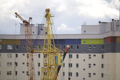 Work on the construction site. A workers` brigade mounts a tower crane. Heavy construction machinery works. Royalty Free Stock Photography