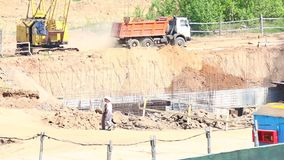 Work on the construction site. Workers are walking, the truck is moving, an excavator is working in the pit. Work on the construction site. Workers are walking stock video